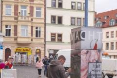 """Gotha / Neumarkt:  Noch am Tag der Vernissage malt und sprüht der Künstler Fab-Jey zwei Bilder auf die Säule MACHT. Sie zeigen den Jugendwerkhof Torgau, eine gefängnisartige Einrichtung,  in der bis 1989 """"schwer erziehbare"""" Jugendliche auf Staatskurs umerzogen wurden."""